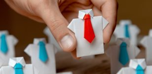 white_buttoned_down_shirts_made_out_of_paper_all_with_blue_ties_except_one_with_a_red_tie_being_picked_up_by_hand